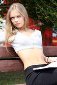 Porträtt av blond ung kvinna sitter på bänken — Stockfoto