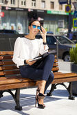 Beautiful business woman sitting on a bench  — Stock Photo