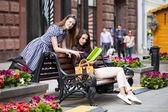 Amigos de garota jovens sentado num banco no centro da cidade — Fotografia Stock