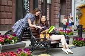 Giovani ragazza amici seduti su una panchina nel centro del paese — Foto Stock