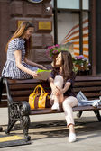 Young girl friends sitting on a bench in the town center  — Stock Photo