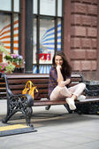 Young woman sits on a bench in the town center  — Foto de Stock