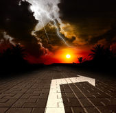 Road with arrow aat the sunset — Stock Photo