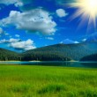 Black lake and grass near by mountians - Stock Photo
