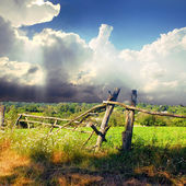 Broken fence on the green field — Stock Photo