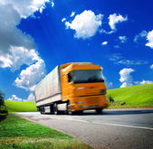Yellow truck on the asphalt road — Stock Photo