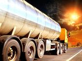 Vozík na rozmazané asfaltové silnici pod modrou oblohou a slunce světlo — Stock fotografie