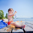 Little girl playing with toys on the wooden pier at the river — Stock Photo #30228591