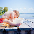 Little girl playing with toys on the wooden pier at the river — Stock Photo #30228611