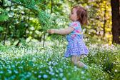 Een klein meisje met een krans in voorjaar bos — Stockfoto