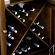 Stacked wine bottles on wooden racks - Stock Photo