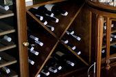 Stacked wine bottles on wooden racks — Stock Photo