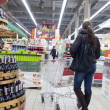 Young woman shopping at supermarket - Stok fotoğraf