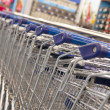 Supermarket shopping carts in a row - Stok fotoğraf