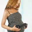 Pregnant woman with headphones on her stomach. - Stock Photo