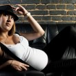 Pregnant woman with suspenders and hat — Stock Photo