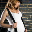 Stock Photo: Pregnant woman with suspenders and hat