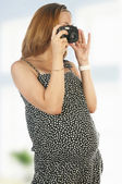 Pregnant woman with photo camera — Stock Photo