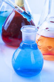 Blue reagent drop into the glass flask — Stock Photo
