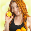 Beautiful girl with red dreadlocks holding oranges in her hands — Stock Photo