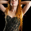 Beautiful girl with red dreadlocks posing in military corset - Stock Photo