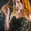 Beautiful girl with red dreadlocks posing in military corset — Stock Photo