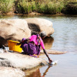 Woman washes dishes in the river. Hampi, India - Stock Photo