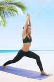 Woman on the beach in Virabhadrasana I position — Stock Photo