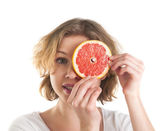 Young woman with the slice of grapefruit in front of eye — Stock Photo