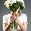 Woman covering  face with a bouquet — Stock Photo