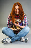 Red haired woman sitting on the floor with ferret — Stock Photo