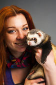 Red haired woman holding ferret — Stock Photo