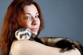 Ferret lying on woman's shoulder — Stock Photo