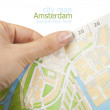 Tourist hand holding Amsterdam Free City map — Stock Photo