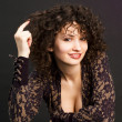 Woman wearing elegant dress curling her hair on finger — Stock Photo