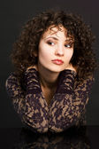 Woman with curly hair holding hands behind her neck — ストック写真