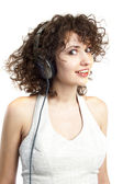 Curly haired woman listening to music with headphones — Stock Photo