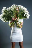 Woman hiding her face behind chrysanthemums — Stock Photo