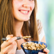 Happy woman eating cereal — Stock Photo