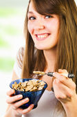 Cheerful woman eating cereal — Stock Photo