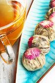 Flowering tea balls and cup of tea — Stock Photo