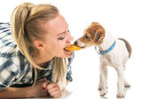 Woman eatting biscuit with puppy — Stock Photo