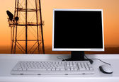PC with sunset sky and electric pylons background — Stockfoto