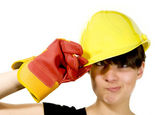 Girl in yellow hard hat and red gloves with funny face — Stock Photo