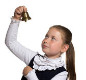 Young school girl looking to golden bell on white background — Foto de Stock