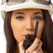 Serious female construction worker talking with a walkie talkie  — Stock Photo