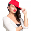 Attractive young woman wearing a red baseball cap — Stock Photo