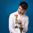 Young man looking to red rose — Stock Photo