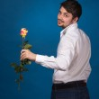 Young man giving a red rose — Stock Photo #26209083