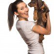Brunette girl with her puppy isolated on white background — Stock Photo